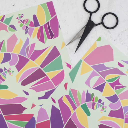 Abstract patterns in the process of being created; a pair of scissors is visible in the photograph.