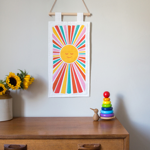 A wall hanging of the sun, with multi coloured rays emitting from its centre.