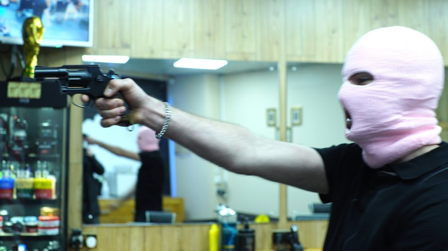 A figure wearing a pink balaclava and black T-shirt points a gun out of shot; a still from the music video for Diamonds Into Dust