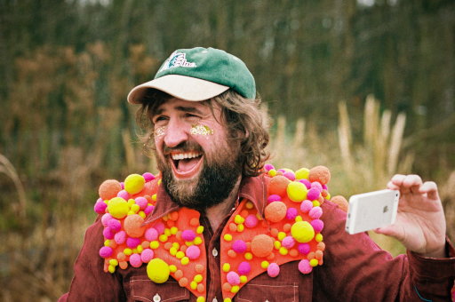 Johnny Lynch of Pictish Trail, wearing a green cap and multi-coloured scarf