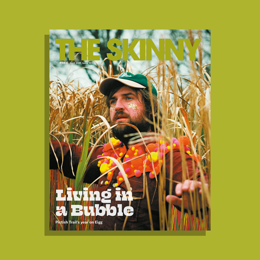The cover of The Skinny's April 2021 issue; Johnny Lynch stands in the centre of the frame, surrounded by tall grass. Headline reads 'Living in a Bubble'