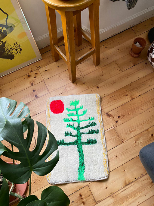 A pale rug decorated with a bright green tree and a red sun sits on a wooden floor. A cheeseplant is in the foreground, with a stool and various art materials placed at the edges of the frame.