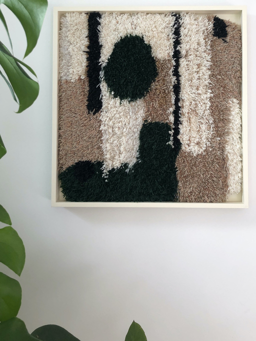 A rug hanging on a wall. The rug is brown with interlocking black and white figurative shapes emerging from the top and bottom. A plant is visible to the left of the rug.