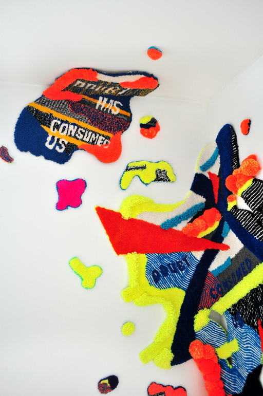 A tufted rug in two parts; a small section of blue and yellow with red flashes, featuring the text 'Doubt Has Consumed Us'. A larger piece of the rug features a variety of thin and thick stripes in blue, yellow and red. The words 'Doubt' and 'Consumed' are visible.
