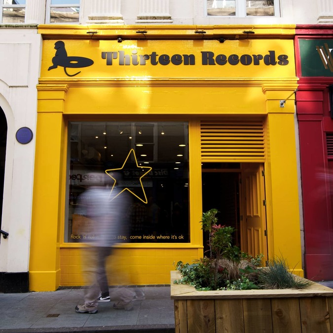 The exterior of Thirteen Records; a yellow painted single-story shopfront, with a large window decorated with a yellow star. A member of the public walks past in the foreground.
