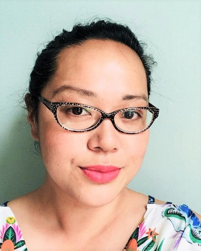 Portrait/ headshot photo of Maisie Kwan against a light green background; Maisie wears tortoiseshell glasses and a floral top.