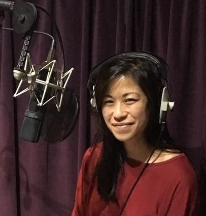 Anna Cheung in what appears to be a recording studio. Anna wears headphones, with a microphone set up in front of her and purple velvet curtains behind.