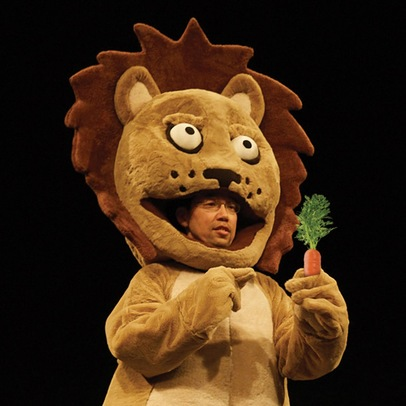 Mamoru Iriguchi, dressed in an oversized lion costume. His face is visible within the lion's mouth, and he holds a prop carrot.