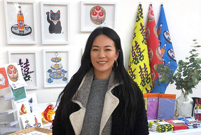 Sarah Kwan stands in front of an array of framed works and assorted stationery.