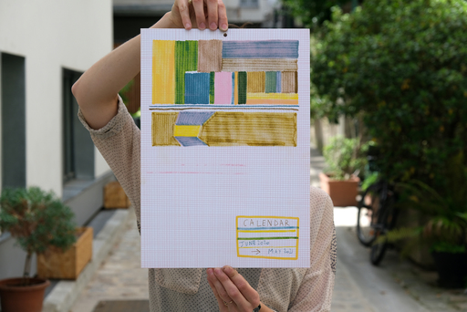 Mari Campistron stands outside in a courtyard, holding a printed calendar in front of her face. The top half of the calendar features blocks of colour arranged in a geometric pattern. The background includes planters and a parked bicycle.