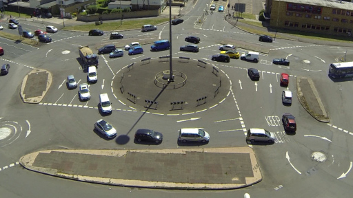 An aerial view of a group of cars gridlocked around a complex system of roundabouts. Image is a still from Aman Sandhu's artwork 'The Magic Roundabout'.