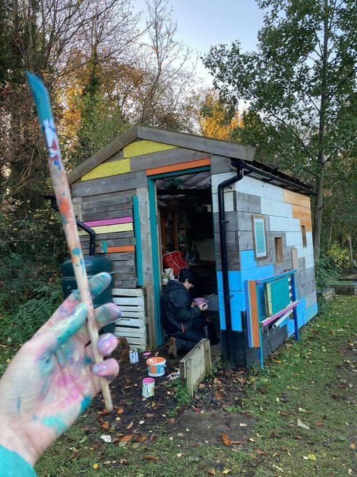 A multi-coloured shed in a wooded area; photographer is holding a paint-covered paintbrush in the foreground, while another person retrieves objects from inside the shed.