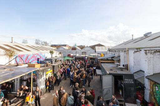 Aerial view of The Pitt street food market; food stalls arranged around a courtyard, with small groups of people scattered around the frame.