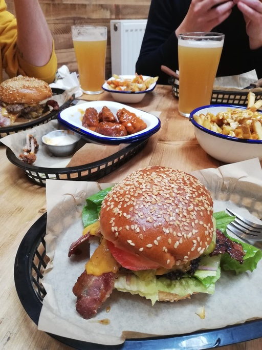 A table of burgers, fries and glasses of beer