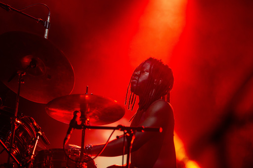 A shirtless Morgan Simpson of black midi plays his drum kit on stage at Edinburgh International Festival.