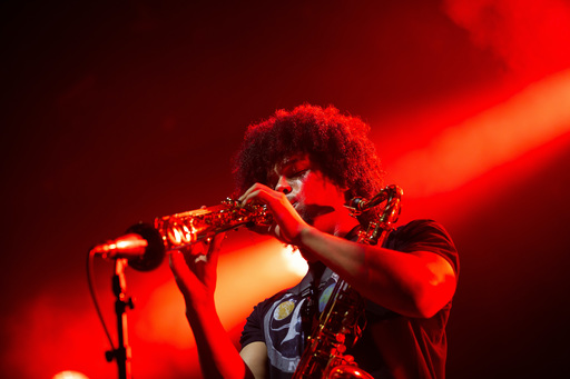 Kaidi Akinnibi of black midi playing a clarinet amid a flash of red and orange light on stage at Edinburgh International Festival. He has a saxophone strapped around his shoulder.