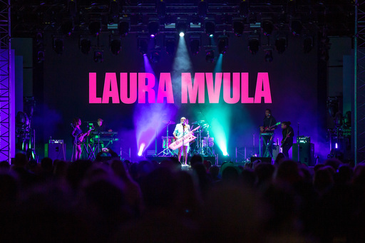Laura Mvula performs at Edinburgh International Festival. A crowd stands in front of the stage; Mvula stands in the centre holding a keytar with various musicians around her. The words 'Laura Mvula' are projected on the screen behind her.