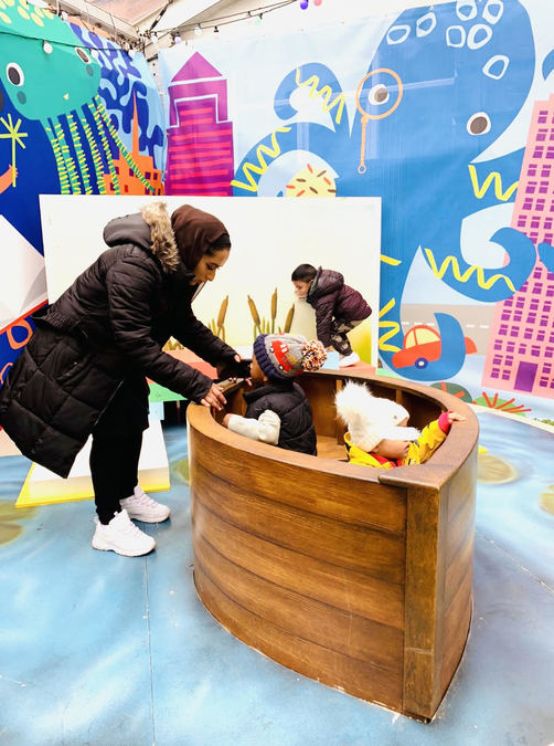 A mother and her child in a play area.