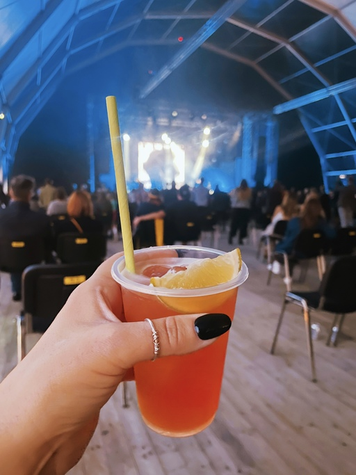 A hand holds an orange drink in front of a concert stage.