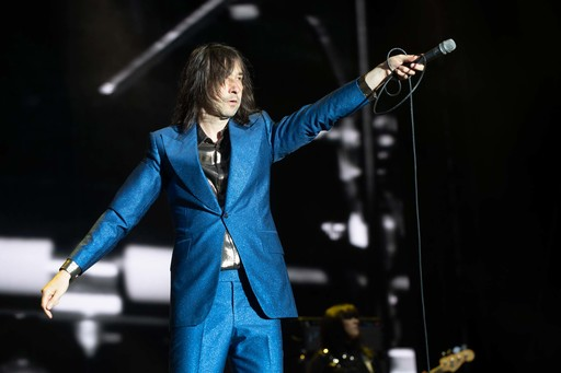 Bobby Gillespie of Primal Scream holds his microphone towards the audience while on stage at TRNSMT festival. He is dressed in a bright blue suit.