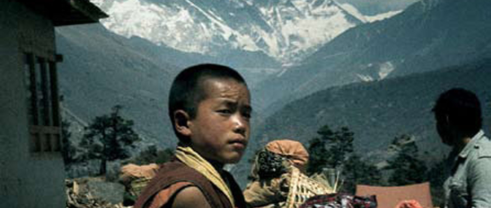 Young novice outside Tengpoche Monastery with Mount Everest in the background, Nepal